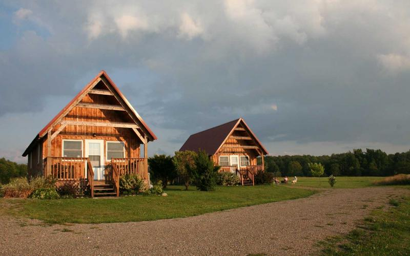 Front of cabins during a summer dusk with visitors relaxing by campfire